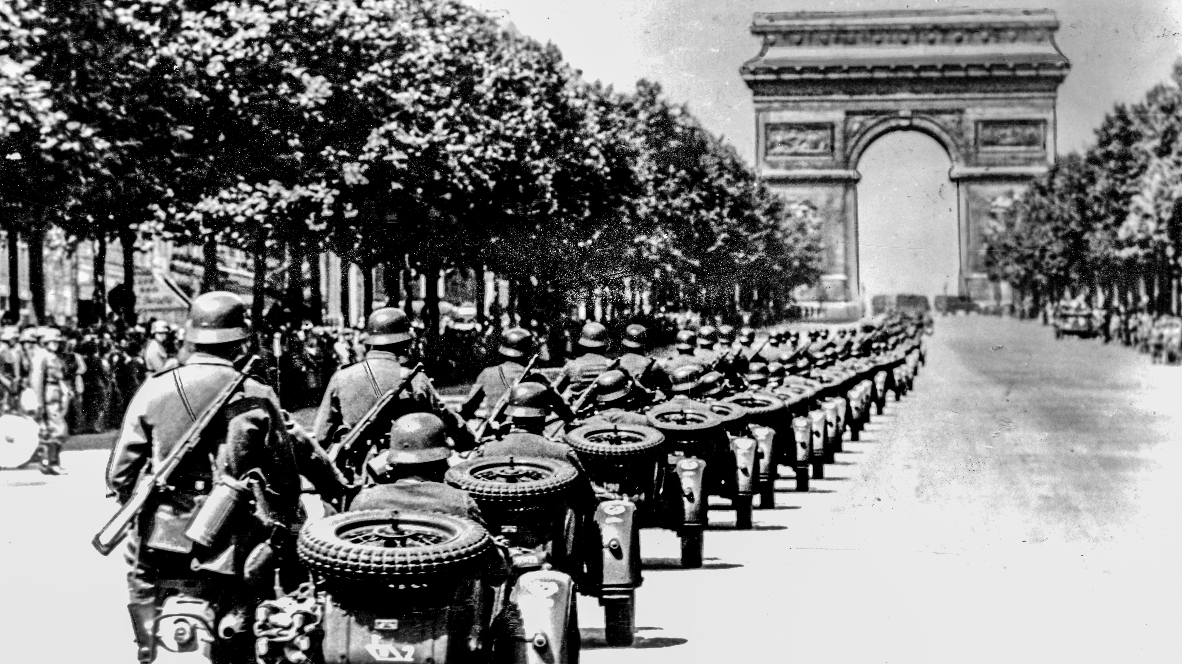 Гитлеровцы победоносно иневстречая никакого сопротивления входят впреданный политиканами Париж. Парад нацистов наЕлисейских полях уТриумфальной Арки, лето 1940года