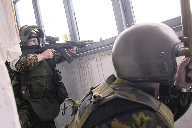 Сотрудник «Альфы» прапорщик Олег Лоськов (слева) ведёт наблюдение зашколой